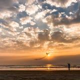 Señora que vuela una cometa en la puesta del sol en la playa de Goa Imágenes de archivo libres de regalías