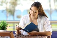 Señora relajada que lee un libro de papel en un balcón Imagenes de archivo