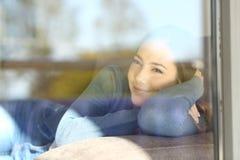 Señora relajada que mira a través de una ventana en casa Foto de archivo