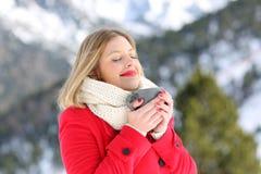 Señora relajada que respira y que sostiene el café en invierno Imagen de archivo libre de regalías