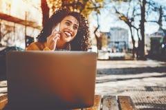 Señora rizada con el ordenador portátil que habla en el teléfono Foto de archivo libre de regalías