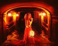 Señora romántica en el rojo que sostiene una linterna en una mazmorra oscura Imagen de archivo libre de regalías