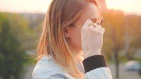 Señora rubia de la vida urbana que goza del parque de la ciudad de la puesta del sol almacen de metraje de vídeo