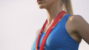 Señora rubia delgada que mira orgulloso adelante, demostrando todo el mundo su medalla metrajes