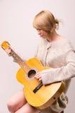 Señora rubia joven en el suéter gris que se sienta en silla y que toca la guitarra acústica Fotografía de archivo