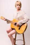 Señora rubia joven en el suéter gris que se sienta en silla y que toca la guitarra acústica Fotografía de archivo libre de regalías