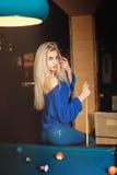 Señora rubia joven sensual que presenta en la mesa de billar con la señal Imagen de archivo