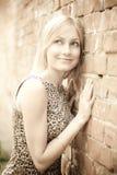 Señora rubia linda que se coloca cerca de una pared de ladrillo foto de archivo