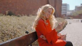 Señora rubia linda Smiling y el mandar un SMS en medios sociales con Smartphone al aire libre almacen de video