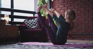 Señora rubia que estira las piernas y que practica yoga en casa en sala de estar, ella tiene un cuerpo apto, y llevar un cómodo almacen de metraje de vídeo