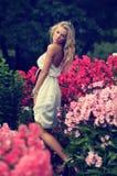 Señora rubia que presenta en flores Imágenes de archivo libres de regalías