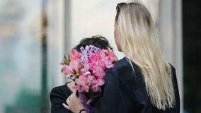 Señora rubia que recibe las flores y enhorabuena en la graduación de universidad almacen de metraje de vídeo