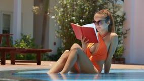 Señora rubia Reads Book Sits en piscina en el hotel turístico
