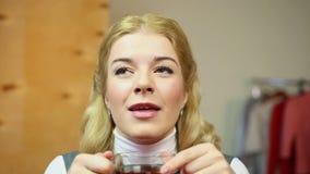 Señora rubia romántica que piensa en su té querido y de consumición en casa almacen de metraje de vídeo