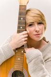Señora rubia sonriente hermosa joven en el suéter gris que toca la guitarra acústica Imagen de archivo libre de regalías