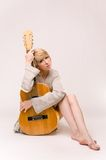 Señora rubia sonriente hermosa joven en el suéter gris que toca la guitarra acústica Imagen de archivo