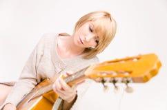 Señora rubia sonriente hermosa joven en el suéter gris que toca la guitarra acústica Fotografía de archivo
