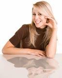 Señora rubia sonriente Sitting en su escritorio Imagen de archivo libre de regalías