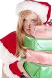 Señora Santa que mira alrededor de presentes de la pila Fotos de archivo