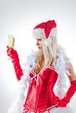 Señora Santa que mira el vidrio del champán Foto de archivo libre de regalías