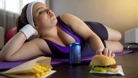 Señora segura de sí mismo gorda que come la comida basura en vez del entrenamiento, falta de motivación foto de archivo