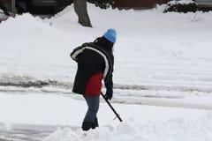 Señora Shoveling Snow de la calzada Fotos de archivo libres de regalías