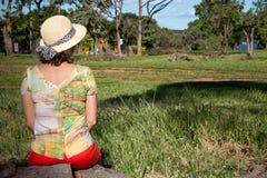 Señora Sitting en un tocón que lleva un sombrero y pantalones cortos que goza de Great Outdoors Fotos de archivo libres de regalías