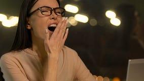 Señora soñolienta sobrecargada que bosteza en el lugar de trabajo, no teniendo ninguna nueva idea, desempleo metrajes