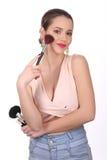 Señora sonriente con el cepillo del maquillaje Cierre para arriba Fondo blanco Imagenes de archivo