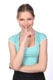 Señora sonriente con el finger en sus labios Cierre para arriba Fondo blanco Foto de archivo libre de regalías