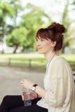 Señora sonriente con la botella de agua que se sienta en banco Imágenes de archivo libres de regalías