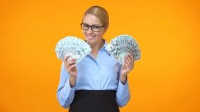 Señora sonriente del negocio que muestra billetes de dólar en el fondo anaranjado, inversión almacen de video