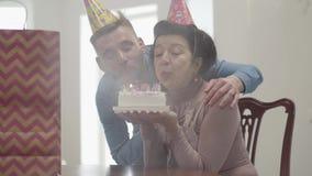 Señora sonriente emocional del retrato que se sienta en la tabla que sostiene la pequeña torta con muchas velas Abrazo adulto del almacen de metraje de vídeo