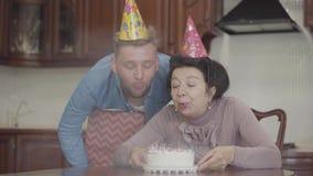 Señora sonriente emocional positiva que se sienta en la tabla que sostiene la pequeña torta con muchas velas Abrazo adulto del ni almacen de video