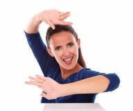 Señora sonriente en camisa azul que gesticula el baile Imagen de archivo