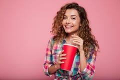 Señora sonriente en los vidrios 3d que bebe la cola aislada sobre rosa Foto de archivo