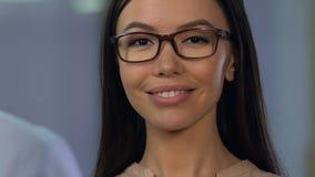 Señora sonriente hermosa en las lentes que miran a la cámara, control de la vista, salud metrajes