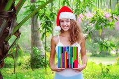 Señora sonriente joven con el reloj coloreado de madera en sombrero de la Navidad fotografía de archivo