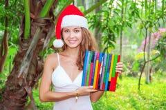 Señora sonriente joven con el reloj coloreado de madera en sombrero de la Navidad fotos de archivo libres de regalías