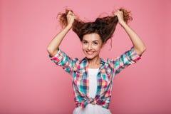 Señora sonriente joven que juega con el pelo rizado y que mira la cámara Fotografía de archivo