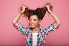 Señora sonriente joven que juega con el pelo rizado y risa aislada Imágenes de archivo libres de regalías