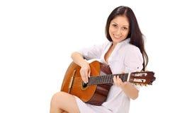 Señora sonriente joven que toca la guitarra acústica imagen de archivo