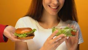 Señora sonriente que elige la ensalada verde en vez de la hamburguesa, concepto de la dieta sana almacen de metraje de vídeo
