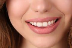 Señora sonriente que muerde su labio Cierre para arriba Foto de archivo