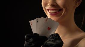 Señora sonriente que muestra tres de as en la cámara, combinación del póker, ganador metrajes