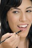 Señora sonriente que pone el lápiz labial Foto de archivo
