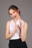 Señora sonriente que presenta con el resbalón del papel Cierre para arriba Fondo gris Imagen de archivo