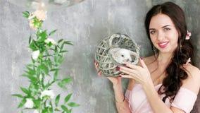 Señora sonriente que presenta para la cámara que sostiene el conejo blanco lindo en la cesta gris de mimbre, sesión de foto de la metrajes