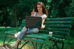 Señora sonriente que se sienta en un banco y la mirada del ordenador portátil Imagen de archivo
