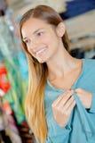 Señora sonriente que sostiene la chaqueta azul de las solapas foto de archivo libre de regalías